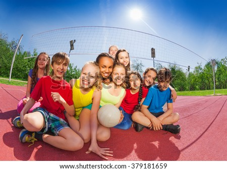 Happy teenagers sitting on volleyball court - stock photo