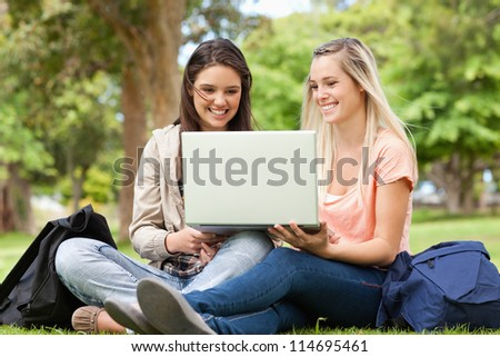 Happy teenagers sitting while using a laptop in a park - stock photo