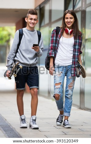 Happy teenagers with skateboards having a city walk in sunny day - stock photo