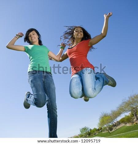 Happy teens jump in air - stock photo