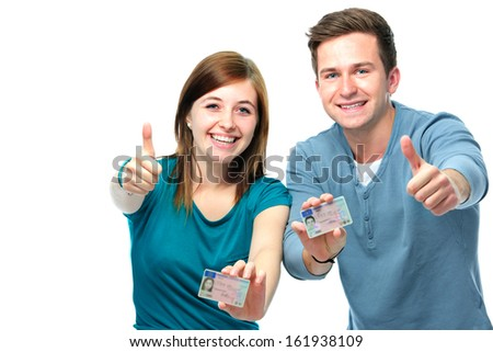 happy teens showing their driving license isolated over white - stock photo