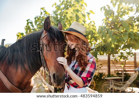 Happy tender young woman cowgirl in hat standing with her horse on ranch