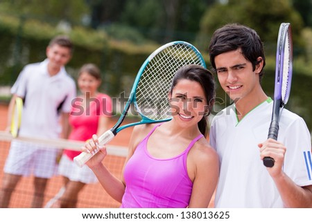 Happy tennis couple playing doubles at the court - stock photo