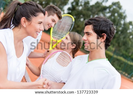Happy tennis players handshaking after a match