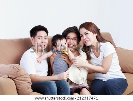 Happy Thai family sitting on the sofa  - stock photo
