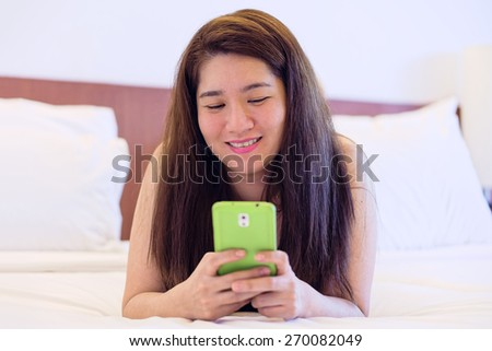 Happy Thai woman is playing and chatting on her mobile phone in a room - stock photo