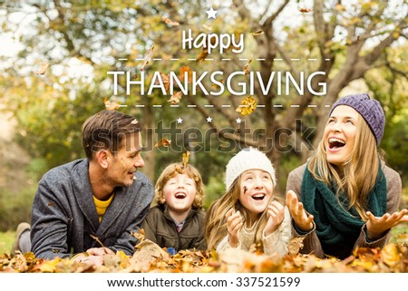 Happy thanksgiving against smiling young family throwing leaves around - stock photo