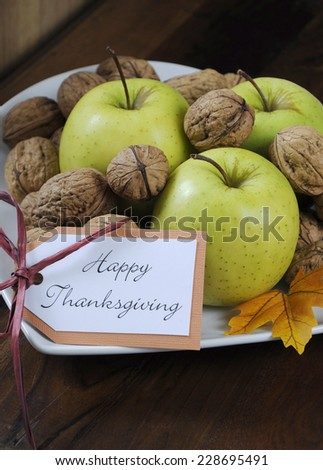 Happy Thanksgiving Autumn Fall harvest fruits with green apples and walnut nuts in white heart shape plate on dark recycled wood background, with copy space. Close up. - stock photo