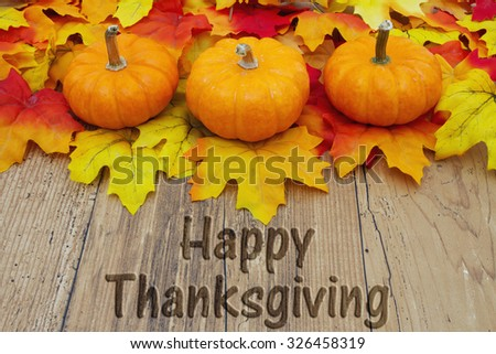 Happy Thanksgiving, Autumn Leaves and Pumpkins on weathered grunge wood with text Happy Thanksgiving - stock photo