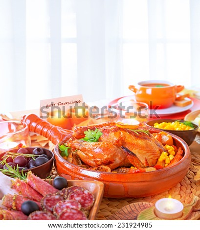 Happy Thanksgiving day, festive table setting with greeting card on it, tasty oven baked turkey and vegetables for holiday dinner, decorated with nice little candle  - stock photo