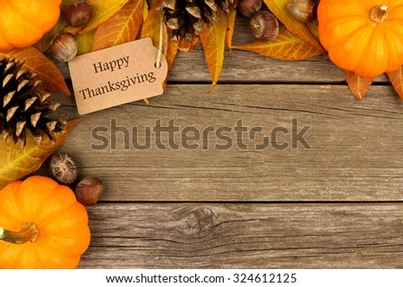 Happy Thanksgiving gift tag with corner border of colorful leaves and pumpkins over a rustic wood background - stock photo