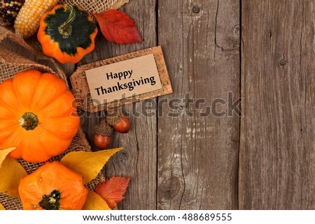 Happy Thanksgiving gift tag with side border of colorful leaves and pumpkins over a rustic wood background