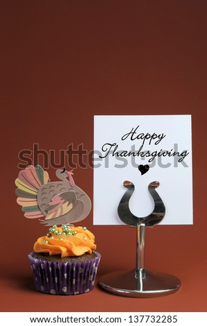 Happy Thanksgiving message on table stand with orange cupcake with turkey decoration. Vertical with copy space for your text here. - stock photo