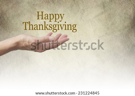 Happy Thanksgiving Parchment banner -   Woman's outstretched hand with palm up and a 'Happy Thanksgiving' floating above on a rustic stone effect background  fading to white - stock photo