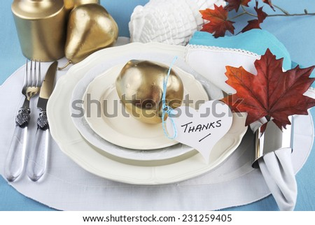 Happy Thanksgiving table place setting in pale aqua blue and white theme with gold fruit and candle - stock photo