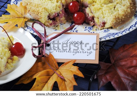 Happy Thanksgiving table setting with cherry apple crumble pie on a vintage blue plate with autumn leaves on blue tablecloth. Close up.