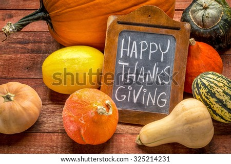 Happy Thanksgiving  - white chalk handwriting on a small blackboard surrounded by pumpkin and winter squash - stock photo