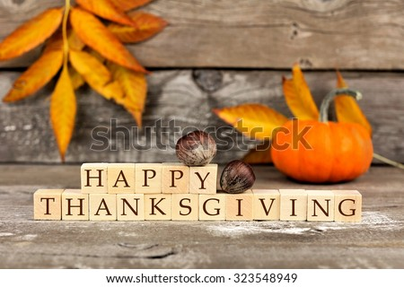 Happy Thanksgiving wooden blocks against a rustic wood background with pumpkins and autumn leaves - stock photo