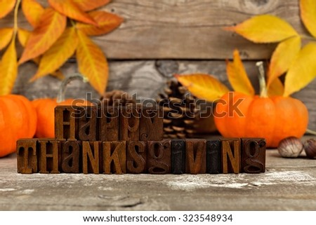 Happy Thanksgiving Wooden Letters Against A Rustic Wood Background With Pumpkins And Autumn Leaves