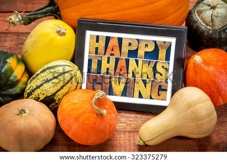 Happy Thanksgiving word abstract in letterpress wood type on a digital tablet surrounded by pumpkin and winter squash - stock photo