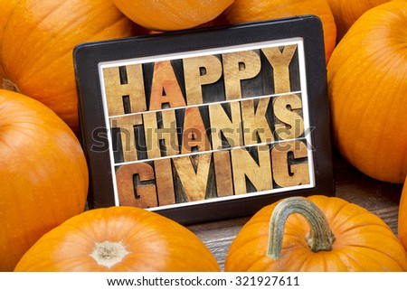 Happy Thanksgiving word abstract in letterpress wood type on a digital tablet surrounded by pumpkins - stock photo