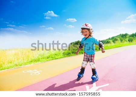 Happy thee years old boy rollerblading in the park on sunny summer day with bike and pedestrian signs on the road - stock photo