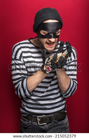 Happy thief holding stolen necklace. Portrait on red background     - stock photo