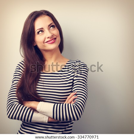 Happy thinking casual girl with folded hands looking up. Closeup vintage portrait with empty copy space - stock photo