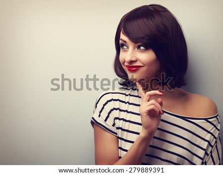 Happy thinking woman looking with finger under face on empty copy space. Closeup vintage portrait - stock photo