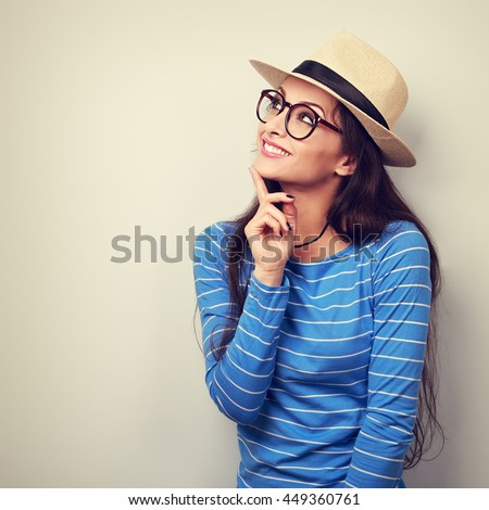 Happy thinking young woman looking up in fashion glasses and straw hat. Vintage toned portrait - stock photo