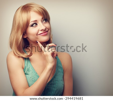 Happy thinking young woman with blond short hairstyle looking with finger under face. Color toned portrait - stock photo