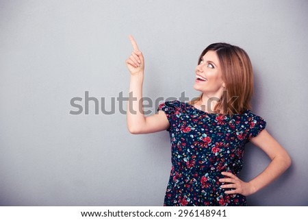 Happy thoughtful woman pointing finger up over gray background. Looking up - stock photo