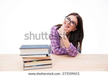Happy thoughtful woman sitting at the table with books and looking up at copyspace - stock photo