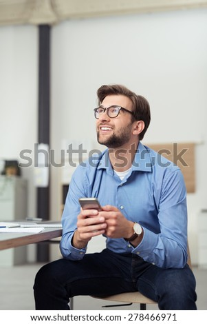 Happy Thoughtful Young Businessman, Sitting on a Chair and Leaning on his Knees, Holding his Mobile Phone and Looking Up. - stock photo