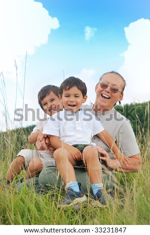 Happy three children in nature with grandmother
