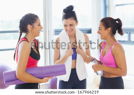 Happy three fit young women chatting in a bright exercise room