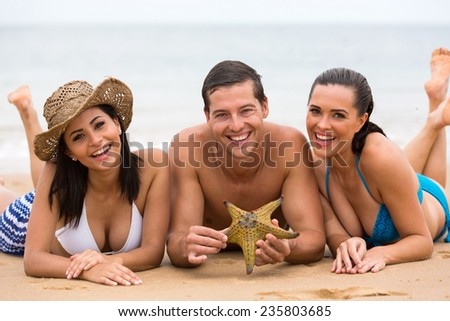 happy three friends lying on beach sand and holding a starfish - stock photo
