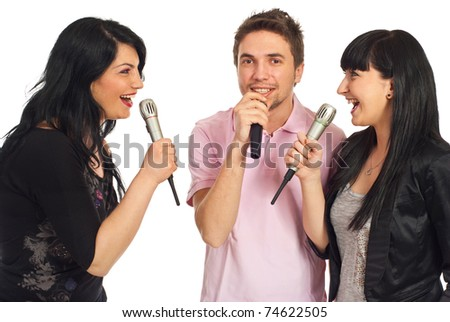 Happy three friends singing in microphones at karaoke party and having fun isolated on white background - stock photo