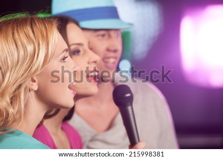 Happy three friends singing in microphones. two women and man having fun isolated in bar  - stock photo