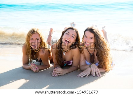 happy three friends teen girls lying on beach sand smiling - stock photo