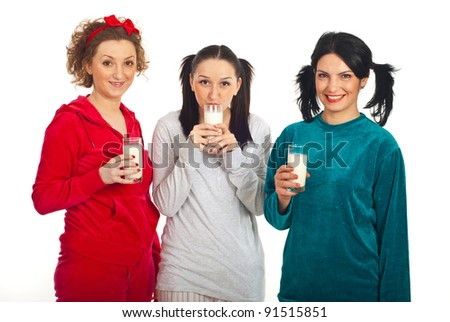 Happy three friends women in pajamas standing in a line and holding milk glasses isolated on white background - stock photo