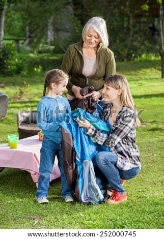 Happy three generation females assembling tent at campsite - stock photo