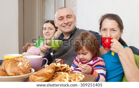 Happy three generations family having tea and cakes at home  - stock photo
