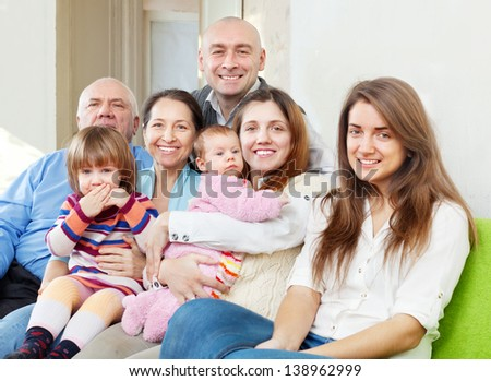 Happy three generations family sits on sofa at home - stock photo