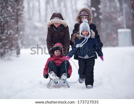 Happy three kids and their mother walking in winter park - stock photo