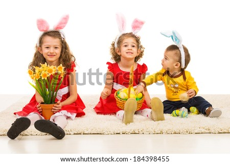 Happy three kids with bunny ears sitting in aline on carpet with Easter eggs - stock photo