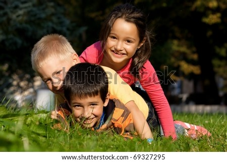 Happy three little friends laying on the grass in the park - stock photo