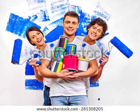 Happy three persons are painting  wall at home. - stock photo