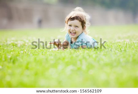 happy three year old child playing  at grass meadow in summer - stock photo