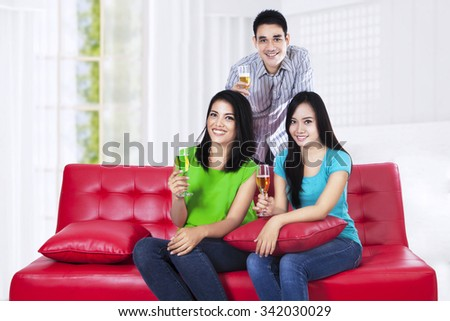 Happy three young friends with wine sitting on red couch - stock photo